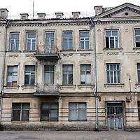 Two women walk down the street in front of an old building in Snipiskes neighborhood of Vilnius, Lithuania