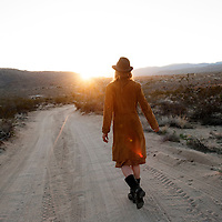 Woman walking towards the sun along a desert road.