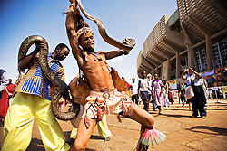 A Tanzanian tribal sorcerer and his assistant, playing a traditional dance with an African Rock Python around the Moi International Sports Complex, during the VII World Social Forum.<br /> Dancers and drummers were dancing and playing whistles.<br /> Nairobi city, Kenya, Africa.