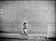 Woman walking on a tile wall in the southern Chiapas border city of Tapachula, Mexico.