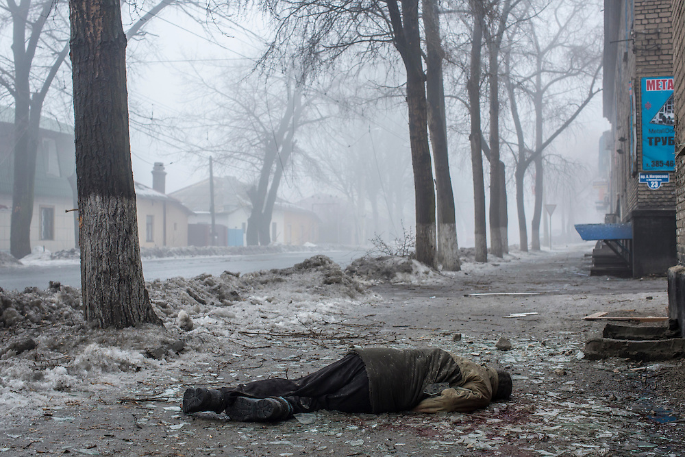 DONETSK, UKRAINE - JANUARY 30, 2015: The body of a man lies on the sidewalk after a rocket or mortar hit the road and exploded in Donetsk, Ukraine. One other man was killed, and at least five people were killed in a separate shelling nearby when a rocket landed in the parking lot of a humanitarian aid distribution center. CREDIT: Brendan Hoffman for The New York Times