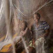 Sainata Ouedraogo (left) and Adama Oudraogo under the mosquito net they share at their home in the village of Bore in the Sanmatenga region of Burkina Faso on 24 February 2014. Mosquito nets greatly decrease the incidence of malaria by reducing the risk of being bitten by the nocturnal Anopheles mosquito, which carries the malaria parasite.