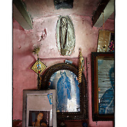 """SHOT 2/6/15 11:47:58 AM - A roadside capilla in the mountains just outside of Mascota, Mexico and featuring Nuestra Señora de Guadalupe as well as pictures of loved ones and personal effects. The Virgin of Guadalupe has symbolized the Mexican nation since Mexico's War of Independence. Our Lady of Guadalupe (Spanish: Nuestra Señora de Guadalupe) is a celebrated Catholic icon of the Virgin Mary also known as the Virgin of Guadalupe (Spanish: Virgen de Guadalupe). The Lady of Guadalupe is of significant importance to Mexican Catholics and has been given the titles of """"Queen of Mexico"""", """"Empress of the Americas"""", and """"Patroness of the Americas"""". Roadside capillas, or tiny chapels, are common along the roads and highways of Mexico which is heavily Catholic and are often dedicated to certain patron saints or to the memory of a loved one that has passed away. Often times they contain prayer candles, pictures, personal artifacts or notes. (Photo by Marc Piscotty / © 2015)"""