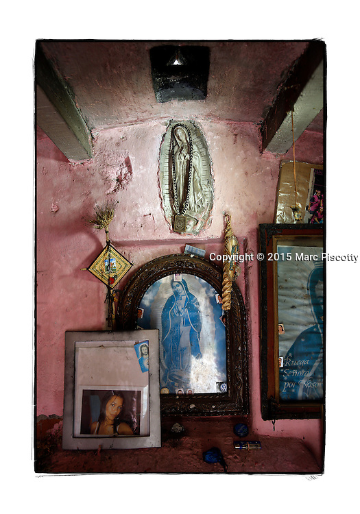 "SHOT 2/6/15 11:47:58 AM - A roadside capilla in the mountains just outside of Mascota, Mexico and featuring Nuestra Señora de Guadalupe as well as pictures of loved ones and personal effects. The Virgin of Guadalupe has symbolized the Mexican nation since Mexico's War of Independence. Our Lady of Guadalupe (Spanish: Nuestra Señora de Guadalupe) is a celebrated Catholic icon of the Virgin Mary also known as the Virgin of Guadalupe (Spanish: Virgen de Guadalupe). The Lady of Guadalupe is of significant importance to Mexican Catholics and has been given the titles of ""Queen of Mexico"", ""Empress of the Americas"", and ""Patroness of the Americas"". Roadside capillas, or tiny chapels, are common along the roads and highways of Mexico which is heavily Catholic and are often dedicated to certain patron saints or to the memory of a loved one that has passed away. Often times they contain prayer candles, pictures, personal artifacts or notes. (Photo by Marc Piscotty / © 2015)"
