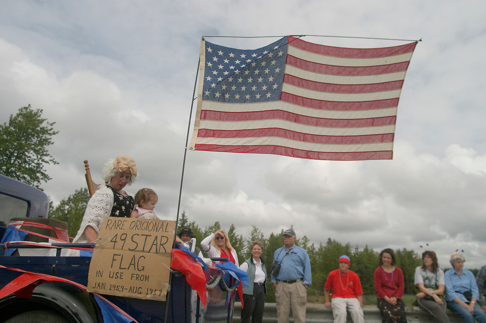 A rare 49 star flag is displayed from a classic car during the fourth of July parade in Gustavus.