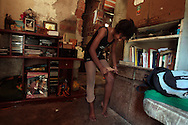 Marie Ellen da Silva adjusts her stockings in her home, before going to her ballet classes, in Santa Teresa neighborhood in Rio de Janeiro August 16, 2012. 'Ballet Santa Teresa', a non-governmental organization (NGO) gives children who live in areas with social risk, some suffering domestic violence, free ballet classes and other activities as a part of socio-cultural integration project.  Photo by: Pilar Olivares