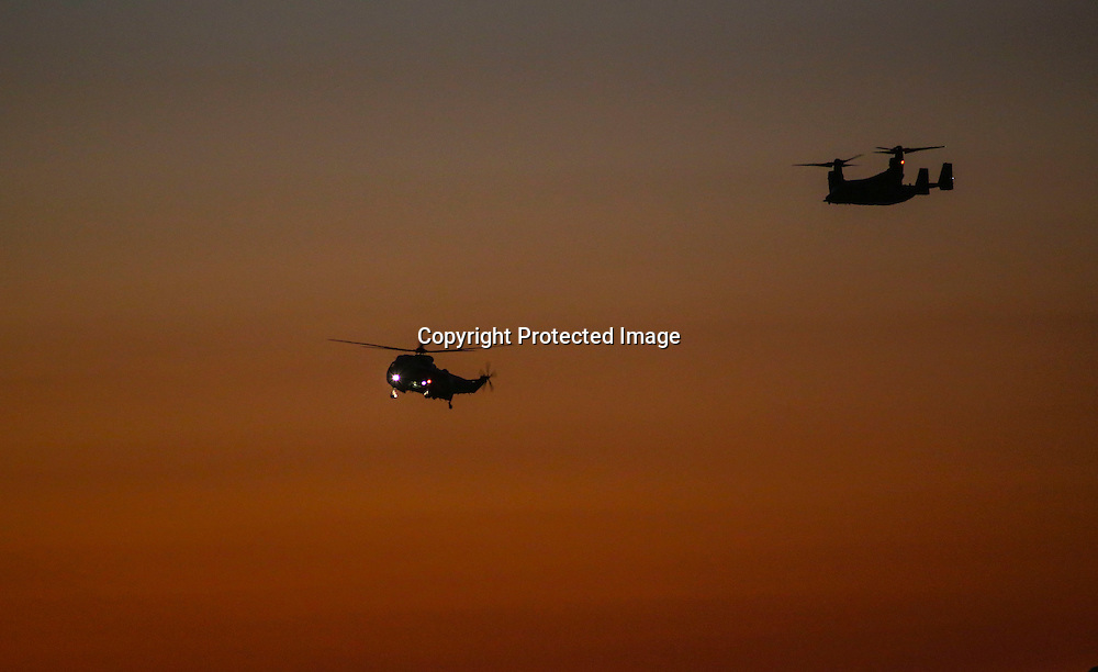"""Marine One, left, with President Barack Obama aboard, is escorted by  an """"Osprey"""" aircrafts as it arrives at  Los Angeles International Airport in Los Angeles on Saturday, Oct. 10, 2015.  (AP Photo/Ringo H.W. Chiu)"""