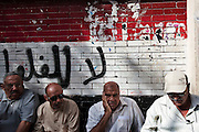 "Egyptian men cue in front of a polling station in the last few minutes before the start of the first truly democratic Presidential election in Egypt's history May 23, 2012 in Cairo, Egypt. Graffiti behind the men translates to ""No felool"", a reference to members of Mubarak's former government and National party members. The election will take place over two days, May 23, and 24th 2012.  (Photo by Scott Nelson)"