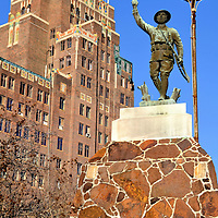 WWI Doughboy Soldier Statue and Threefoot Building  in Meridian, Mississippi<br /> Shortly after WWI, more than 150 copies of a pressed copper sculpture called the Spirit of the American Doughboy were erected throughout the U.S.  The soldier is shown carrying his rifle and holding a grenade over his head.  The backdrop of this statue in Meridian, Mississippi, is the Threefoot Building.  In 1929, it was the town&rsquo;s pride.  Today, it stands in ruins but the exquisite art deco features can still be seen around the broken windows.