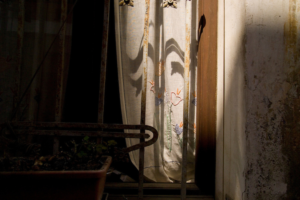 Sunset light streaming into room and on to window with white embroidered curtain and a rusted iron frame in front of it. Sundown shadows cover wall and room with small table hiding in the shadowed corner. Peeling white washed walls with dark wall exposed.