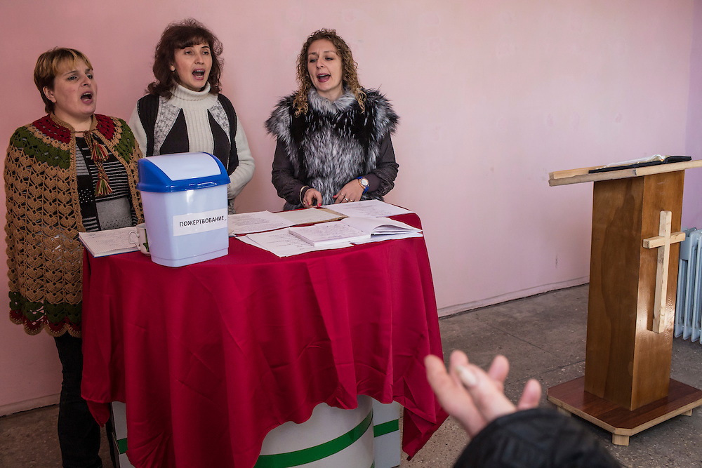 MARIINKA, UKRAINE - FEBRUARY 20, 2016:  Congregants sing during a service at the Christian Help Center of the Church of the Transfiguration in Mariinka, Ukraine. The Donetsk suburb has been the scene of some of the heaviest fighting recently between Ukrainian forces and pro-Russian rebels. CREDIT: Brendan Hoffman for The New York Times