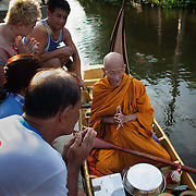 Thai Buddhist monk Luang Pho Malai, 91 years old, offers a blessing to the faithful during his morning rounds Saturday, June 29, 2013.  For the past 30 years Luang Pho Malai has made his daily round to attend to the faithful using a small wooden boat to collect their offers and dispense blessings.  While many of Bangkok's major canals were filled in and paved over during the building boom of the 1980's, Klong Thavi Watthana still serves the needs of an impoverished community.
