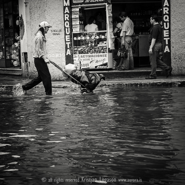 Man in Merida walking with groceries through pool of water that the drain system cant get out of the way fast enough after a heavy rain fall