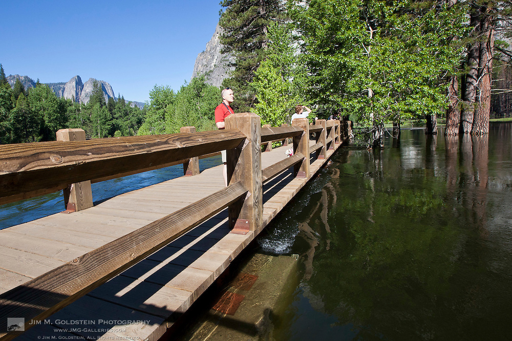 Tourists standing atop Swinging Bridge barely above the Merced River at flood stage - Yosemite National Park, California