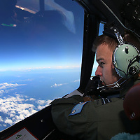 PERTH, AUSTRALIA - MARCH 26:  RAAF Flight Lieutenant Russell Adams looks out from the cockpit of an AP-3C Orion whilst on a search mission in the Southern Indian Ocean on March 26, 2014 in Perth, Australia. The search for flight MH370 resumes today after rough winds and high swells prevented crews from searching for debris yesterday. Six countries have joined the search, now considered to be a recovery effort, after authorities have announced that the airliner crashed in the Southern Indian Ocean and that there are no survivors.  (Photo by Paul Kane/Getty Images)