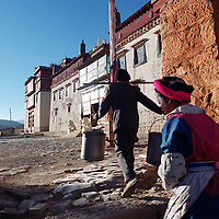 """ZHONGDIAN COUNTY, DECEMBER 19, 2000: Tibetans walk through the gate of Songzanlin monastery, Yunnan province , December 19, 2000..Zhongdian county is believed to be part of the areas on which James Hilton's famous novel """" lost Horizon""""- a description of Shangri-La- is modelled.. ."""