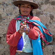 Woman spinning yarn in the village of Sunchubamba, a Quechua speaking native community in Southeastern Peru that is running a reforestation plot in the Andes near Cusco and the Interoceanic Highway.