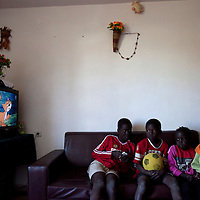 """The Aguek children, Sudanese refugees, watch a cartoon on the sudanese chanel in their living room in the SinSin building on February 28 2011 in Eilat. The municipality hung 1,500 red flags around the city as a sign of warning and put up hundreds of banners reading: """"Protecting our home, the residents of Eilat are drawing the line on infiltration."""" Eilat Mayor Meir Yitzhak Halevi said that 10 percent of the city's population was currently made up of migrants and that the residents feel that the city has been conquered...Photo by Olivier Fitoussi."""