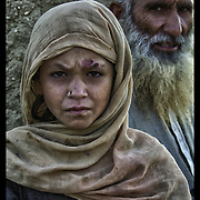 A young Afghan girl is watched closely by her father as she is photographed near her home in the Shomali Valley, Aug. 29th, 2002.