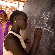 Female teacher looking over a girl who solves a math problem on the black board during class at the Tangory Transgambienne 2 primary school in the town of Bignona, Senegal on Wednesday June 13, 2007.