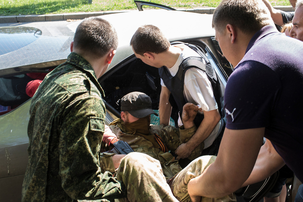 DONETSK, UKRAINE - MAY 26: An injured pro-Russian separatist fighter is loaded into a car outside the Donetsk airport, scene of an hours-long battle between pro-Russian separatists and Ukrainian forces, on May 26, 2014 in Donetsk Ukraine. A day after businessman Petro Poroshenko won Ukraine's presidential election, separatists occupied the airport, leading to a military response. (Photo by Brendan Hoffman/Getty Images)