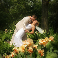 Groom dipping bride among the flowers