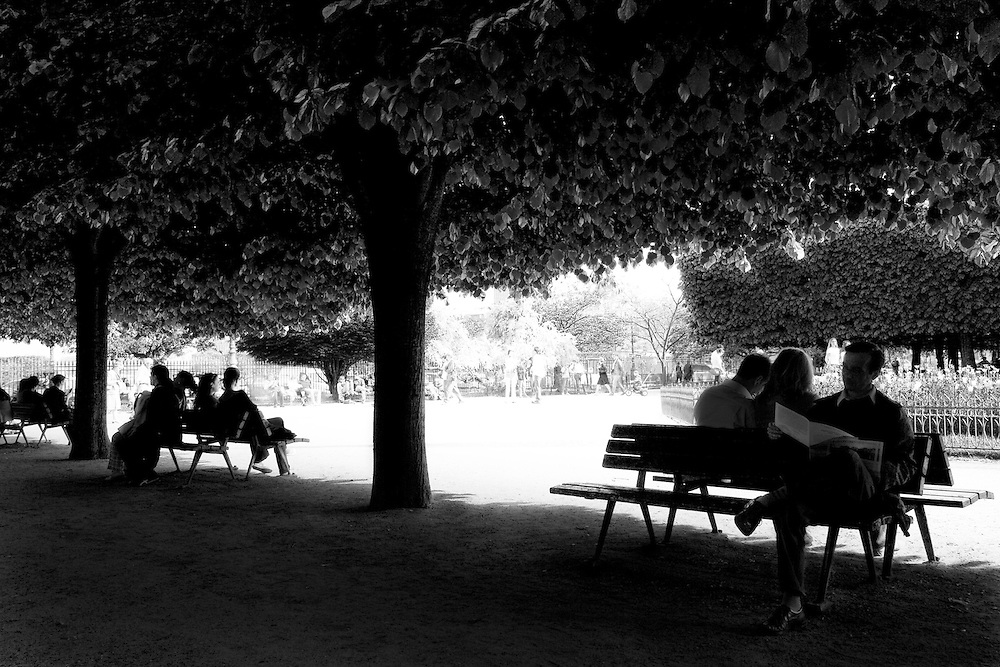 """Silhouettes of people relaxing and enjoying the shade sitting on park benches at the tree lined flower garden behind Notre Dame """"Our Lady"""" or Notre Dame de Bonne-Nouvelle, """"our lady of good news"""", Paris, France next to the River Siene."""