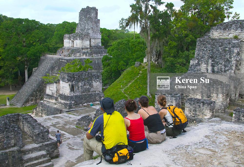 Tourists looking at Temple II sitting on north Acropolis, Tikal, Guatemala