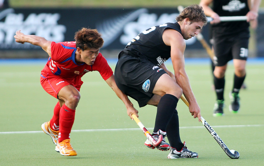 New Zealand's Nick Wilson, right, looks to beat Korea's Nam Yong Lee during their international hockey match at Lloyd Elsmore Hockey Stadium, Auckland, New Zealand, Thursday, February 09, 2012. Credit:SNPA / Ben Campbell..