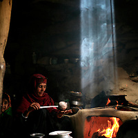 A Gujjar woman makes salt tea in her hut as a shaft of light beams down through the smoke.