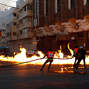Fire fighters try to extinguish a fire that witnesses say was caused by an Israeli air strike in Gaza City.
