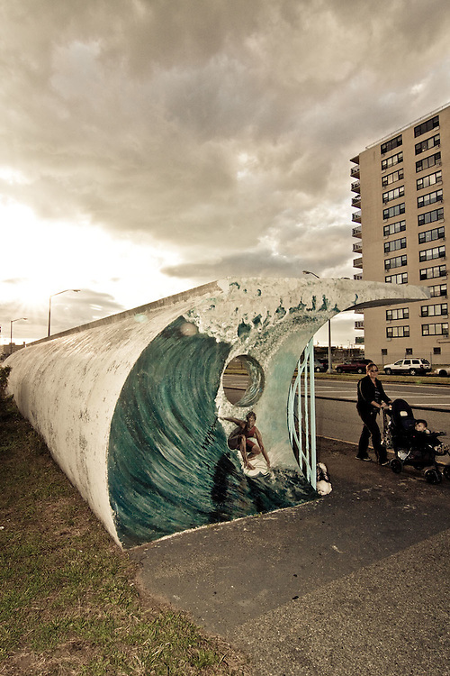 A mother pushes her baby in a carriage undeneath a bus shelter resembling a wave in Rockaway Beach, Queens, NY.