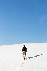 Athletic man running on a sand dune in White Sands, NM
