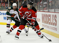 Mar 20, 2009; Newark, NJ, USA; New Jersey Devils left wing Zach Parise (9) skates with the puck by Minnesota Wild center Eric Belanger (25) during the second period at the Prudential Center.