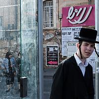 A young Orthodox Jewish man walks along Mea Sharim St in Jerusalem