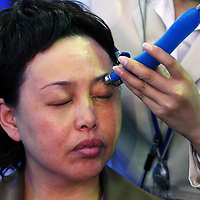 BEIJING, 22. October 2004 : a woman enjoys a facial treatment by a professional at the International Beauty Week in Beijing, October 22, 2004, in China. Beauty business is booming in China. Sales in beauty related businesses and products are worth more than 7 billion USD last year.      ..Whereas in Mao Zedong's China, even pigtails were seen as a sign of vanity (and had to be cut off) , nowadays, urban Chinese women seek about every means in order to distinguish themselves from the masses.  This year Beijing will organize the worl'd first beauty pageant for women who had plastic surgery in early December...