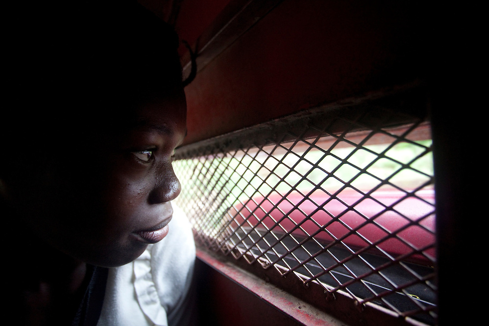 A girl stares through the grated window of a tap tap in Haiti