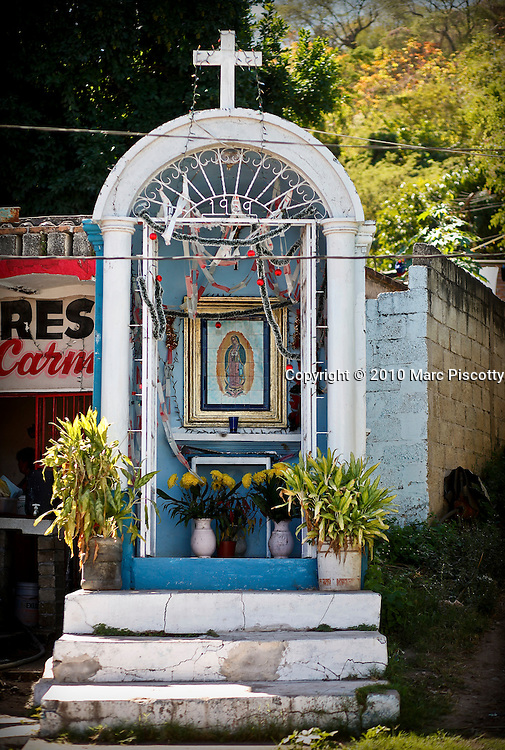 """SHOT 1/30/10 1:33:57 PM - A small capilla decorated for Christmas in the town of Ruiz, Mexico along Highway 15. The Virgin of Guadalupe has symbolized the Mexican nation since Mexico's War of Independence. Our Lady of Guadalupe (Spanish: Nuestra Señora de Guadalupe) is a celebrated Catholic icon of the Virgin Mary also known as the Virgin of Guadalupe (Spanish: Virgen de Guadalupe). The Lady of Guadalupe is of significant importance to Mexican Catholics and has been given the titles of """"Queen of Mexico"""", """"Empress of the Americas"""", and """"Patroness of the Americas"""". Roadside capillas, or tiny chapels, in the Mexican states of Nayarit, Sinaloa and Sonora. The capillas are common along the roads and highways of Mexico which is heavily Catholic and are often dedicated to certain patron saints or to the memory of a loved one that has passed away. Often times they contain prayer candles, pictures, personal artifacts or notes. (Photo by Marc Piscotty / © 2010)"""
