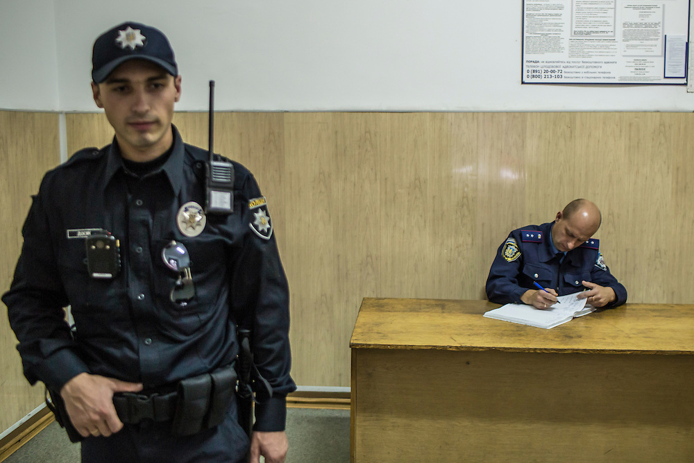 LVIV, UKRAINE - SEPTEMBER 16, 2015: A member of the new Lviv police, left, and the old police, right,  at a police station in Lviv, Ukraine. In an effort to reform the notoriously corrupt Ukrainian police force, an entirely new force has been established in several cities, including Kiev and Lviv, with a primary focus on patrolling the streets. CREDIT: Brendan Hoffman for The New York Times