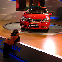 Chinese boy dreaming at the Beijing Motorshow.