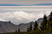 At 12,198 feet (3718m) , the highest peak of Tenerife, and indeed Spain, is Mount Teidi (Pico del Teide) located in the Province of Santa Cruz de Tenerife. The skies can be clear above the clouds below. The moisture from the regular cloud cover means that the tree line reaches high up the mountain sides in form of woods and forest.