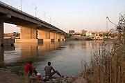 Iraq men fish the Tigris river at dusk under the al-Sinak bridge in downtown Baghdad, Iraq  August 26, 2010.   .