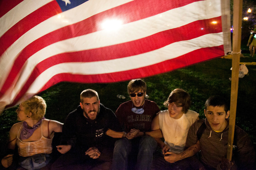 Occupy Boston members gather and link arms under the American flag not to be evicted as the Boston Police evict them in Boston, Massachusetts, Octiber 11, 2011.