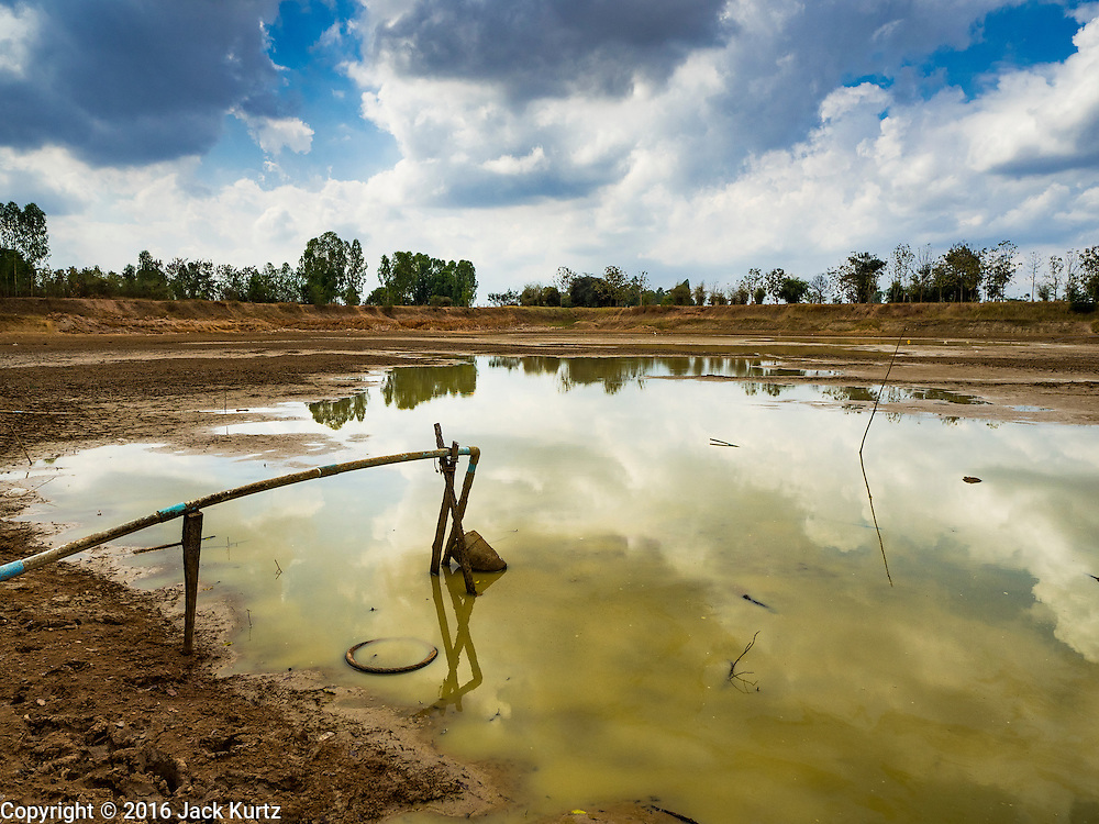 19 JANUARY 2016 - SI LIAM, BURI RAM, THAILAND: The community reservoir in Si Liam, Buri Ram, is lower than it has ever been forcing residents to find an alternative source of domestic water. The reservoir, which is rain fed, is not expected to refill until the rainy season starts in May, leaving the community without water for four months. The drought gripping Thailand was not broken during the rainy season. Because of the Pacific El Nino weather pattern, the rainy season was lighter than usual and many communities in Thailand, especially in northeastern and central Thailand, are still in drought like conditions. Some communities, like Si Liam, in Buri Ram, are running out of water for domestic consumption and residents are traveling miles every day to get water or they buy to from water trucks that occasionally come to the community. The Thai government has told farmers that can't plant a second rice crop (Thai farmers usually get two rice crops a year from their paddies). The government is also considering diverting water from the Mekong and Salaween Rivers, on Thailand's borders to meet domestic needs but Thailand's downstream neighbors object to that because it could leave them short of water.         PHOTO BY JACK KURTZ