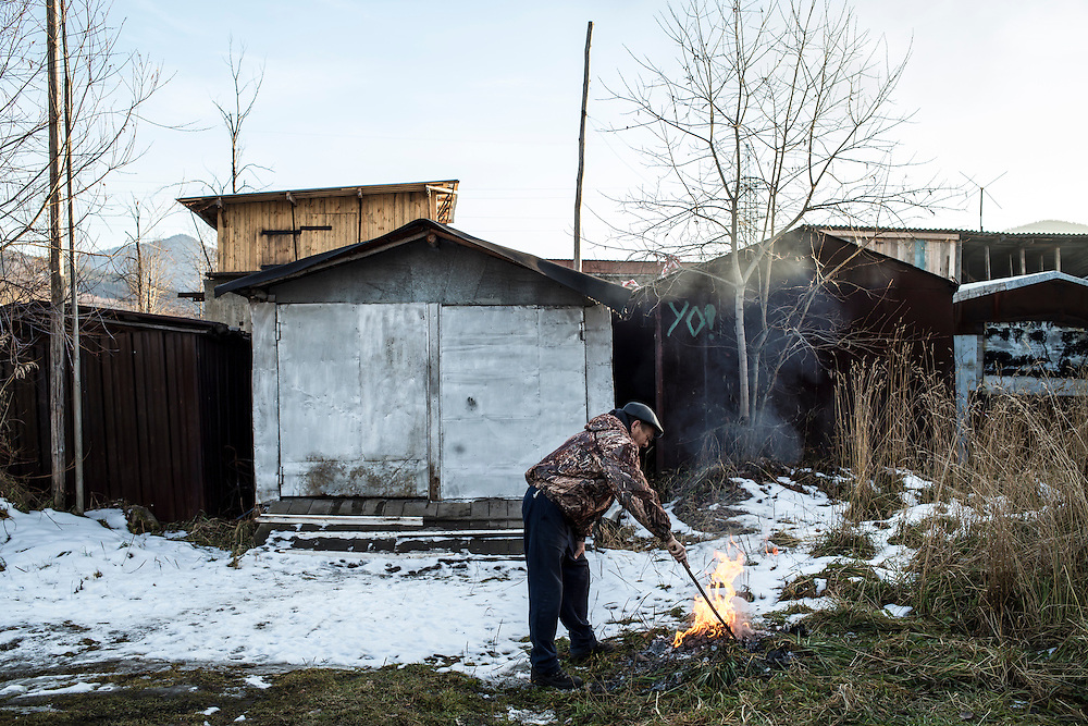 A man burns papers behind his garage on Thursday, October 24, 2013 in Baikalsk, Russia.