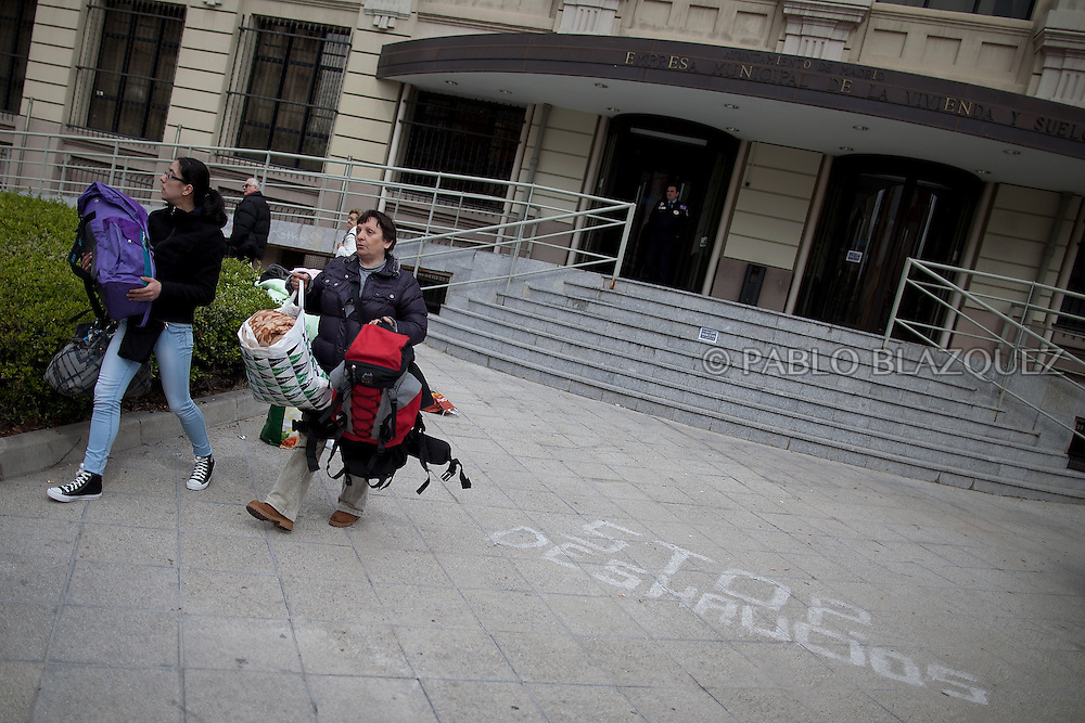Amalia Torres 51, (R) and a friend carry their belongings one day before her eviction takes place outside the Madrid's Council Housing Office where she spent the night claiming to stop her eviction on April 3, 2013 in Madrid, Spain. Graffiti reads 'Stop Evictions'. The Mortgage Holders Platform (PAH) and other anti evictions organizations are organizing 'escraches' since several weeks ago outside Popular Party deputies houses and offices to demand the vote for a Popular Legistative Initiative (ILP) to stop evictions, regulate dation in payment and social rent.