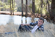 good looking man resting in tall grass by a pond