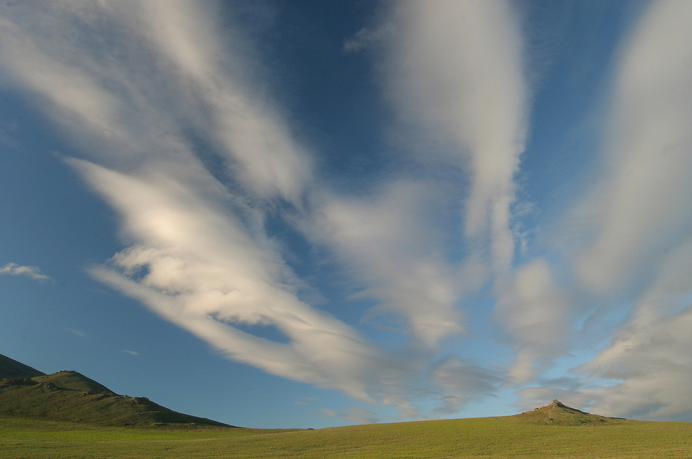A wide angle shot of the vast, open tundra beneath blue skies and white clouds.