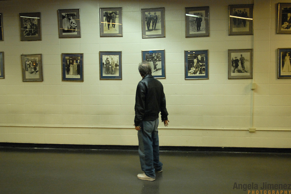 A horse gambler peruses historic photos, mostly from the racing heyday of the 1930s through 1950s, which hang on the wall of the indoor Grandstand area at the Aqueduct race track in New York City on February 18, 2007...Betting on the horses is still a popular game and the money still flows, but off track betting and other forms of entertainment have eroded live attendance at the races.  The daily diehard betters and horse lovers who sparsely populate the place on work days are joined by a bigger crowd on the weekends. ..The Aqueduct, located in Ozone Park, Queens, is the only horse racing track in New York City and probably the coldest in the country (most of the others are in Kentucky, Florida or California). Horses race on the winterized inner dirt rack from January 1st through the end of April. Aqueduct was built in 1894, renovated in 1959, then opened for winter racing in 1975. It is the winter race track operated by the New York Racing Association (NYRA), which also runs Belmont and Saratoga in the warm seasons. Betters at Aqueduct watch and bet on the nine daily live races and all other races around the country via Simulcast. ..