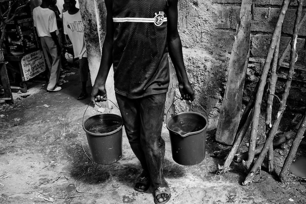 A young man carries buckets of water in a camp for those displaced by the recent earthquake in Petionville, outside Port-au-Prince, Haiti.